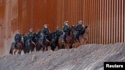 美国一支边境巡逻队沿着边境墙巡逻