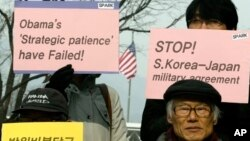 Protesters hold placards during denouncing military alliance between South Korea, the United States and Japan, Seoul, Jan. 15, 2013.