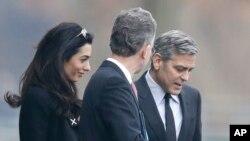 Aktor Amerika George Clooney (kanan) dan istrinya Amal, bersama penasihat kebijakan kanselir Angela Merkel, Christoph Heusgen, di Berlin (12/2). (AP/Markus Schreiber)