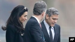 U.S. actor George Clooney, right, and his wife Amal Clooney, left, are accompanied by Merkel's foreign policy advisor Christoph Heusgen as they leave chancellery after private meeting with German chancellor Angela Merkel in Berlin, Germany, Feb. 12, 2016.