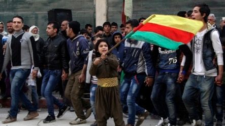 Một cậu bé người Kurd vui mừng vẫy cờ vì thắng lợi trước Nhà nước Hồi giáo ở Kobani.