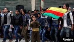 A Kurdish boy waves a Kurdish flag during celebrations after it was reported that Kurdish forces took control of the Syrian town of Kobani, in Sheikh Maksoud neighborhood of Aleppo, Jan. 27, 2015.