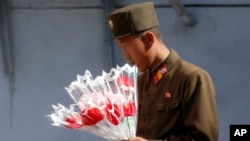 朝鲜一名士兵10月9日手持一束点缀用花朵。朝鲜定于10月10日举行纪念朝鲜劳动党70周年大阅兵。