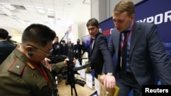 """FILE - A member of the Norh Korean armed forces inspects a submachine gun """"Vityaz-SN"""" at the stand of Russian state-owned arms exporter Rosoboronexport during the annual Moscow Conference on International Security (MCIS) in Moscow, Russia, April 4, 2018."""