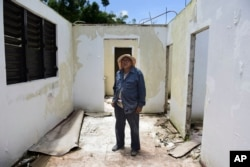 Tinsmit Otoniel Ramos Aponte pozira snimatelju, 16 maja 2018, u svom domu, koji je ostao bez krova tokom udara uraana Marija, ali koji se nije kvalifikovao za federalnu pomoć za obnovu u Jabukoi, gradu u kome i dalje mnogo ostaju bez struje, u Portoriku.