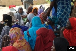 Women sit under a tree waiting for Hajia Hawa to give them free food. Many of them have malnourished children, Maiduguri, Nigeria, Sept. 2016. (Photo: C. Oduah)