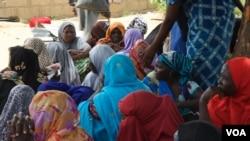 Quelques femmes assises attendent la distribution de nourriture dans un camp, Maiduguri, Nigeria, septembre 2016. (Photo: C. Oduah)