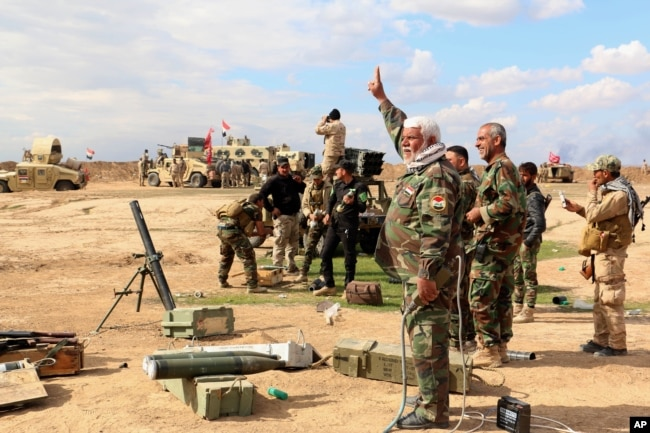 Iraqi army soldiers and volunteers, such as Iranian-backed Shiite militias and Sunni tribes, prepare to launch mortar shells and rockets against Islamic State militant positions outside Tikrit, March 4, 2015.