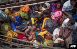 FILE - This photograph taken Sept.12, 2017, shows Rohingya refugees arriving by boat at Shah Parir Dwip on the Bangladesh side of the Naf River after fleeing violence in Myanmar.