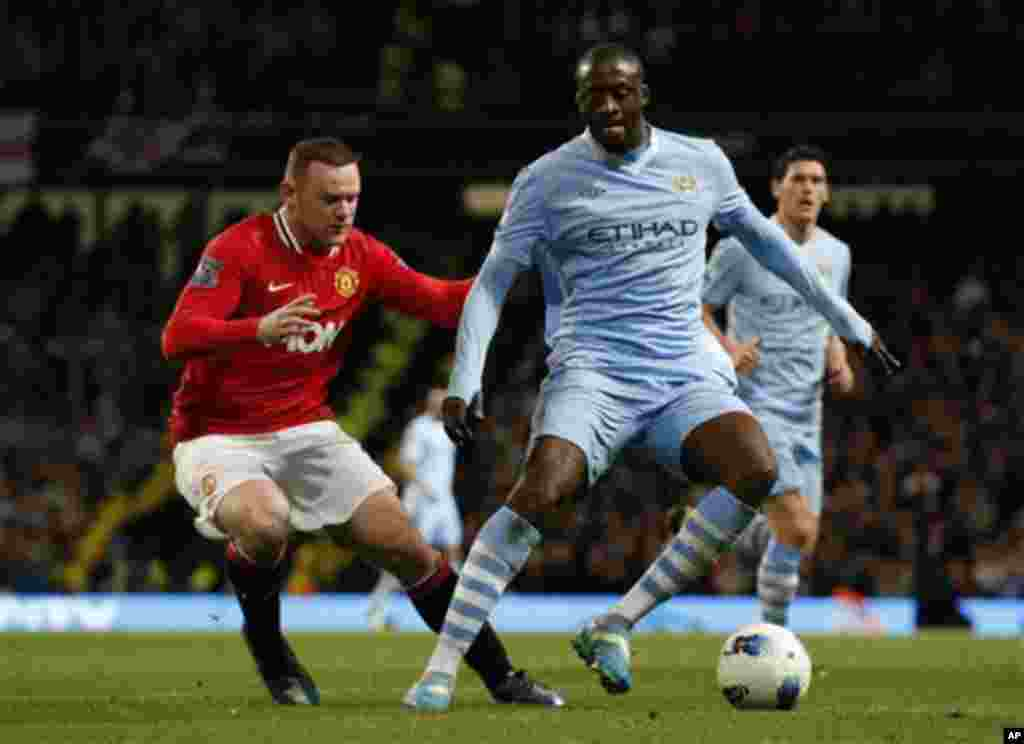 Manchester City's Yaya Toure, right, competes for the ball with Manchester United's Wayne Rooney during the English Premier League soccer match between Manchester City and Manchester United at the Etihad Stadium in Manchester, Monday, April 30, 2012. (AP