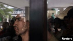 Seorang pengungsi dari etnis Hazara melihat keluar dari belakang panel kaca di tempat penampungan sementara di Karawang, Jawa Barat. (Foto: Ilustrasi)