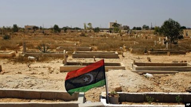 A rebel flag is installed at the tomb of a fighter killed during fighting with forces loyal to Moammar Gadhafi in rebel-held Benghazi, Libya, July 17, 2011