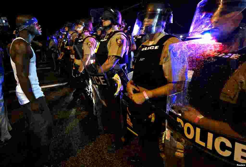 Polisi St. Louis County dan pasukan patroli jalan raya Missouri berjaga-jaga di tengah demonstrasi di di West Flourissant di Ferguson, negara bagian Missouri (10/8). (VOA/Kane Farabaugh)
