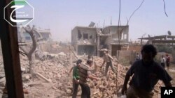 In this May 18, 2013 citizen journalism image provided by Qusair Lens shows Syrians inspecting the rubble of damaged buildings due to government airstrikes, in Qusair, Homs province.