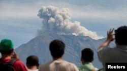 Warga mengamati Gunung Agung mengepulkan asap dan abu vulkanik dari pos pengamatan di Rendang, Kabupaten Karangasem, Bali (foto: dok).