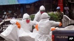 利比里亚的卫生工作者把疑似死于埃博拉的病人的尸体抬上卡车