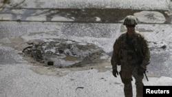 Seorang tentara NATO berdiri di lokasi bom bunuh dire di Kabul, Afghanistan, 11 Oktober 2015. (REUTERS/Mohammad Ismail)