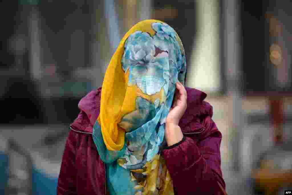 스모그 적색경보가 발령된 중국 베이징에서 한 여성이 스카프로 얼굴을 가린 채 걷고 있다.