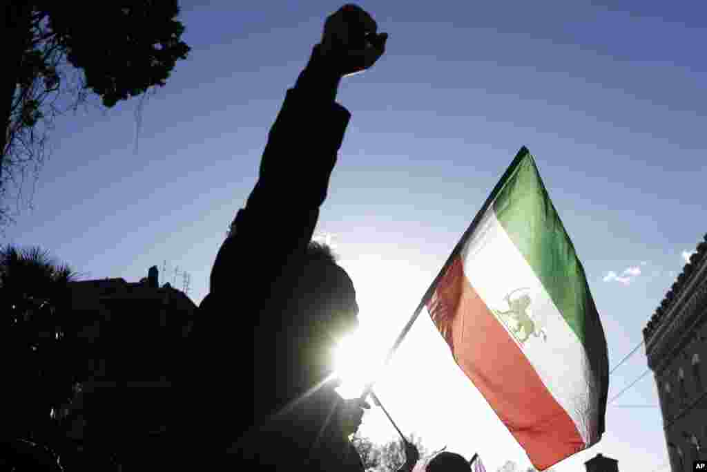 A demonstrator yells slogans near the flag of the former Imperial State of Iran as he gathers with supporters of Maryam Rajavi, head of the Iranian opposition group National Council of Resistance, outside the Iran Embassy, in Rome, Jan. 2, 2017.
