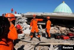 Tim SAR melakukan pencarian korban gempa yang diperkirakan tertimbun di dalam bangunan masjid di Pemenang, Lombok, 8 Agustus 2018.