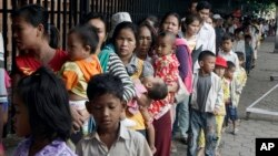 Cambodian villagers line up for medical check-ups outside the children hospital of Kuntha Bopha, in Phnom Penh, July 11, 2012. (AP Photo/Heng Sinith)