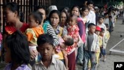 Cambodian villagers for countryside line up as wait for a medical check-up outside the children hospital of Kuntha Bopha, in Phnom Penh, Cambodia, Wednesday, July 11, 2012. A deadly form of a common childhood illness has been linked to many of the mysteri