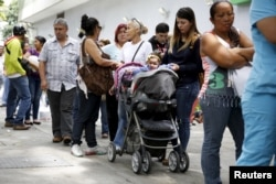 A mother takes care of her daughter while lining up outside a drugstore to buy diapers in Caracas, July 21, 2015.