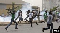 Para demonstran anti pencabutan subsidi BBM di Lagos berlarian setelah polisi Nigeria menembakkan gas air mata (16/1).