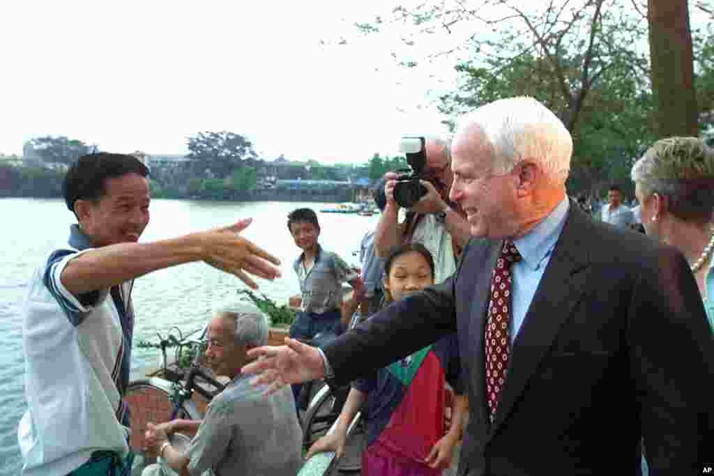 """Thượng nghị sĩ John McCain bắt tay chào một người dân trên bờ hồ Trúc Bạch ở Hà Nội, ngày 26 tháng 4 năm 2000. """"Kiểm tra tình trạng bức tượng của tôi lúc nào cũng là điều tốt,"""" ông nói với phóng viên của AP, nhắc tới tấm bia dựng tại hồ này kỉ niệm sự kiện ông bị bắn rơi vào năm 1967. """"Đó là bức tượng duy nhất mà tôi có,"""" ông nói và cười tươi. Chuyến đi Việt Nam này của ông diễn ra không lâu sau khi ông rút khỏi cuộc đua giành đề cử tổng thống của Đảng Cộng hòa vào đầu tháng 3 sau những thất bại liên tiếp trước ứng cử viên đồng đảng George W. Bush."""