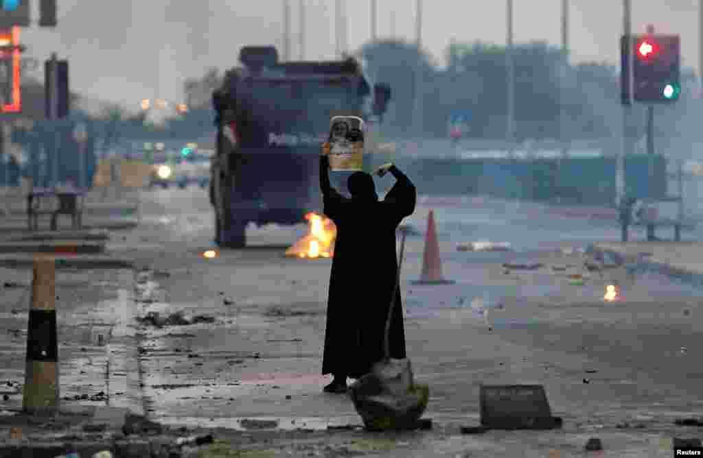បាតុករស្រីម្នាក់កាន់រូបបញ្ញវន្ត Shi'ite ដែលមានឈ្មោះថា Isa Qassim នៅពេលនាងប្រឈមនឹងឡានប៉ូលិសកុបកម្ម ក្នុងពេលបាតុកម្មមួយដើម្បីប្រារព្ធខួបលើកទី៦នៃចលនាបះបោរថ្ងៃទី១៤ កុម្ភៈ នៅក្នុងភូមិ Sitra ប្រទេសបារ៉ែន (Bahrain)។