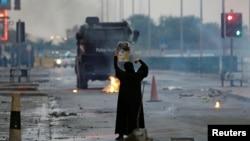 بحرین میں ایک خاتون شیعہ راہنما کے پوسٹر کے ساتھ احتجاج کررہی ہے۔ اپریل 2017