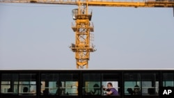 A man yawns in a bus which drives past a construction site in Beijing, China, April 29, 2014.