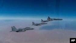지난 26일 미국 루이지애나주 박스데일 공군기지에서 출격한 B-52 스트래토포트리스 폭격기(오른쪽)가 사우디 아라비아 공군 F-15A 전투기들의 호위를 받으며 페르시아만 영공에서 비행하고 있다.