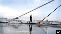 Seorang perempuan berjalan di sekitar kapal yang tertambat di pelabuhan Piraeus dekat Athena, Yunani, saat berlangsungnya pemogokan umum 24 jam sebagai protes atas pemotongan anggaran oleh pemerintah (6/11).