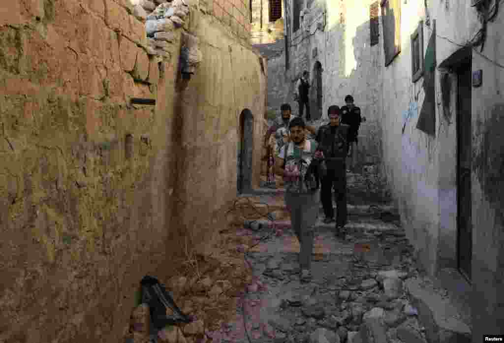Free Syrian Army fighters walk with their weapons along a street around Hanano Barracks in Aleppo, Sept. 10, 2013.