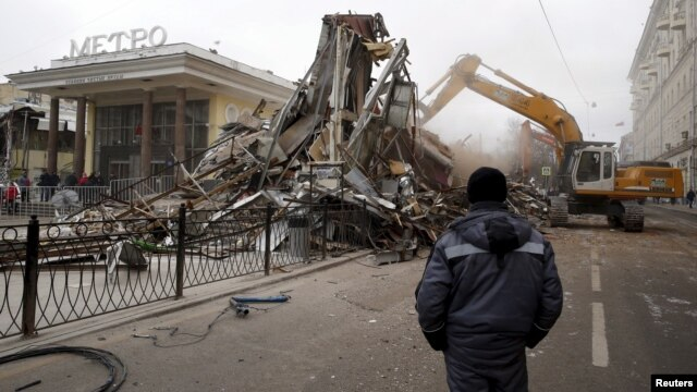 A worker watches as an excavator is used to demolish illegal street kiosks and stalls near Chistiye Prudy metro station in Moscow, Russia, Feb. 9, 2016.