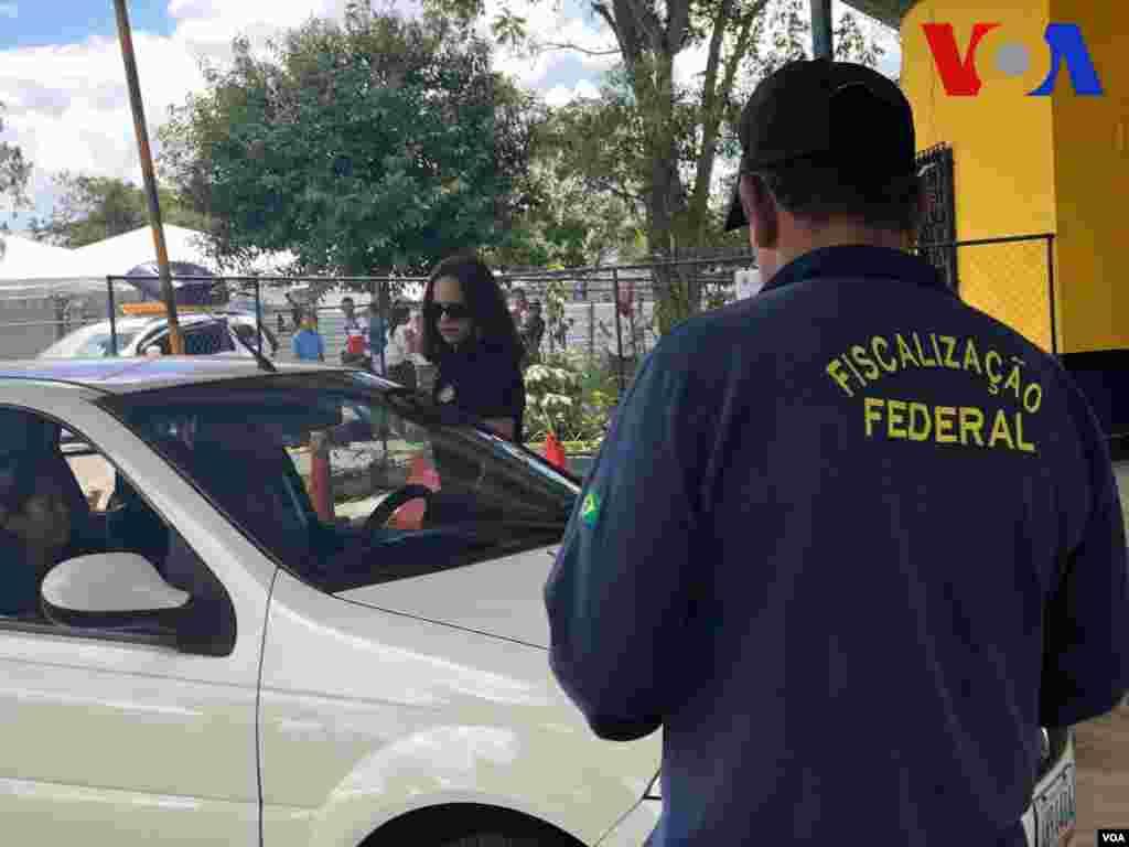 Policía loca realiza un revisión de rutina a un carro en el punto de control de la frontera en Pacaraima, Brasil. Foto: Celia Mendoza - VOA