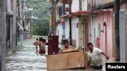Warga memindahkan perabot rumah tangga melalui jalanan yang terendam banjir di Tixtla, Meksiko (19/8).