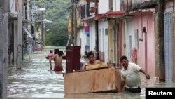 Người dân di chuyển đồ đạc qua một con đường bị ngập lụt ở Tixtla, Mexico, 19/9/2013