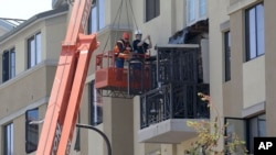 Workers with BELFOR Restoration Company look at a fourth floor balcony railing as it rests on the balcony below at the Library Gardens apartment complex in Berkeley, California, June 16, 2015.