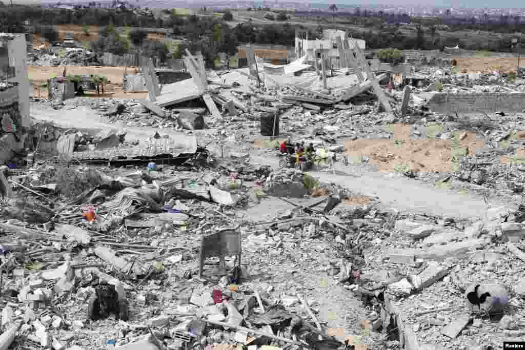 Palestinians ride a donkey cart past the ruins of houses which witnesses said was destroyed during the Israeli offensive in Johr El-Deek village near the central Gaza Strip.