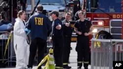 4月16日波士顿消防队员,右,与联邦调查局人员及犯罪现场摄影师谈话