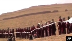 A mass gathering of monks chanting prayers and draping blessing scarves [Khatags] on the body of the deceased monk ahead of his March 19 cremation.