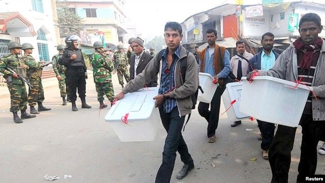 Members of the election commission remove election material after hearing news of a possible attack on polling booths by protesters in Bogra, Jan. 5, 2014.