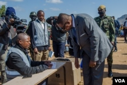 FILE - Then-President Peter Mutharika gets instructions on how to vote from a presidisng officer, in Thyolo district. (Lameck Masina/VOA)