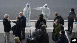 调查新冠病毒源头的世卫专家们抵达武汉天河国际机场,身穿防护服的中国工作人员给他们指方向。(2021年1月14日-美联社)