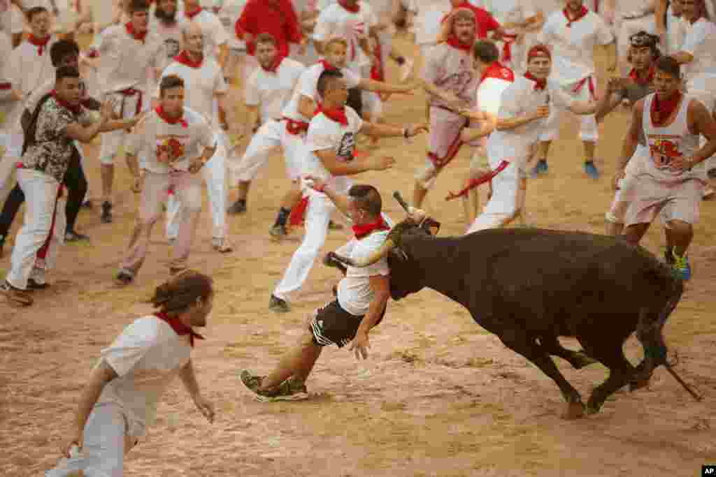 A reveler is charged by a bull during the running of the bulls of 2016 San Fermin fiestas in Pamplona, Spain.