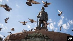 Pigeons fly over a statue of the late Paul Kruger in Church Square, Pretoria, South Africa, Dec. 13, 2018.