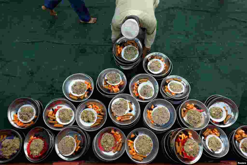 A volunteer arranges food plates for the people to break fast during the fasting month of Ramadan at a mosque in Karachi, Pakistan, May 7, 2019.