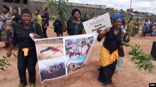 Women protest holding up a poster with images of atrocities committed in an ongoing conflict between government forces and armed separatists, in Bamenda, Cameroon, Sept. 7, 2018. (M.E. Kindzeka/VOA)